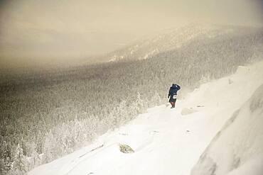 Caucasian hiker waking on snowy hillside