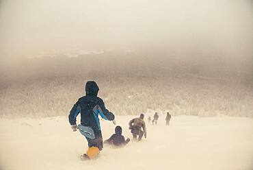 Caucasian hikers walking on snowy hill