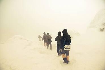 Caucasian hikers walking on snowy path