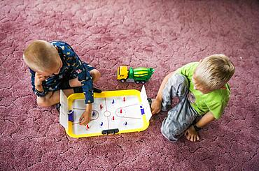Caucasian brothers playing hockey game on floor