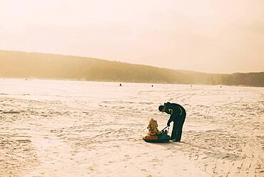 Caucasian father and daughter playing in snowy field