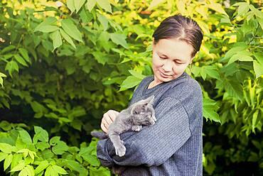 Caucasian woman petting cat in garden