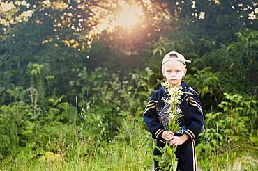 Caucasian boy picking flowers in rural field