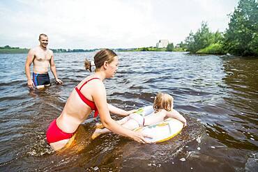 Caucasian family swimming in lake