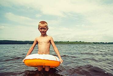 Caucasian boy playing in inner tube in lake