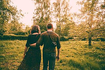 Caucasian couple walking in field