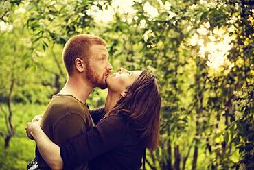 Caucasian couple hugging near trees