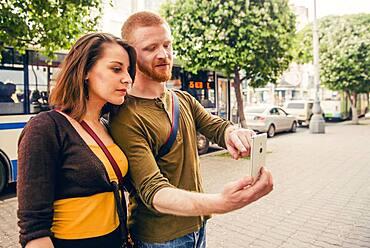 Caucasian couple using cell phone on city sidewalk