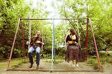 Caucasian couple playing on swing set