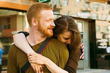 Caucasian couple hugging on city sidewalk