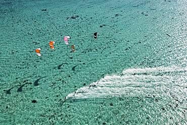 Aerial view of people kitesurfing on ocean