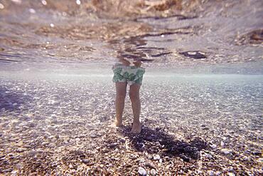 Underwater view of Caucasian girl standing in ocean