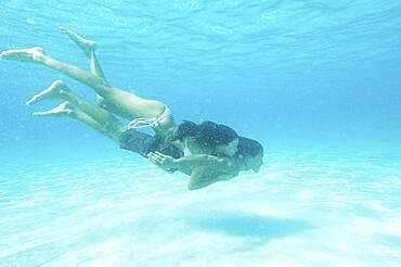 Underwater view of couple swimming in ocean