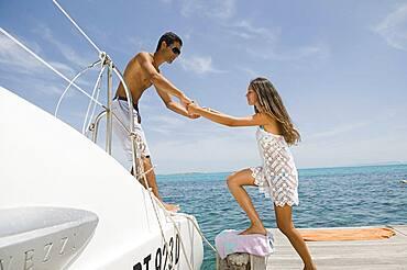 Man helping girlfriend into sailboat on harbor