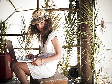 Woman using laptop in beach hut