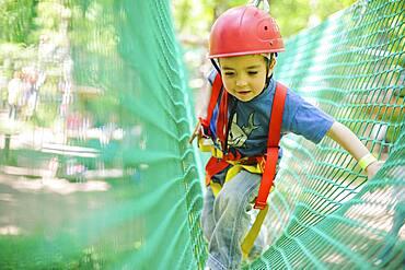 Caucasian boy in harness climbing on net