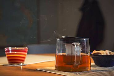 Steaming pot of tea on table