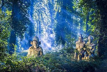Sunbeams on ancient statues in lush forest