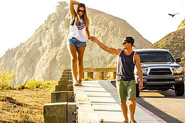 Caucasian man assisting woman walking on railing