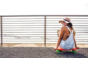 Caucasian woman sitting on skateboard at beach
