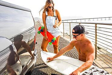 Caucasian couple waxing surfboard
