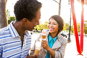Smiling couple eating ice cream in park