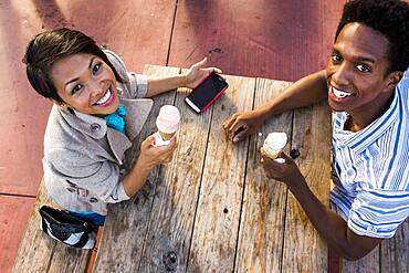 Couple eating ice cream and using cell phone at picnic table