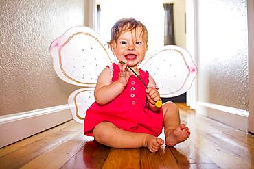 Caucasian baby girl playing in fairy wings