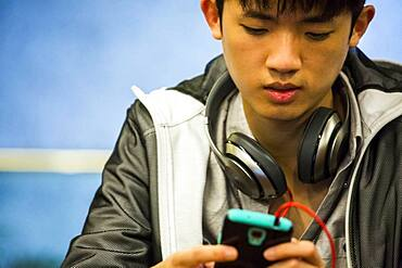 Asian man with headphone using cell phone