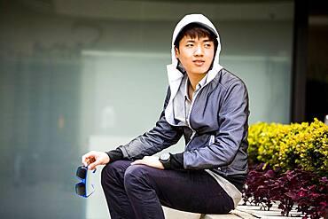 Asian man waiting in city
