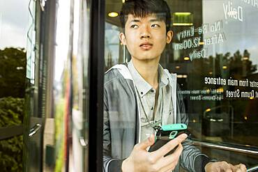 Asian man holding cell phone in doorway