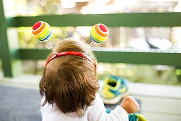 Caucasian baby girl on porch wearing multicolor ball headband