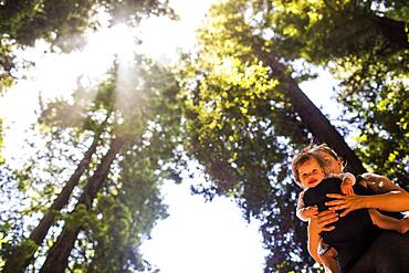 Caucasian mother holding baby girl under trees