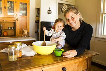 Caucasian mother and baby girl baking in kitchen