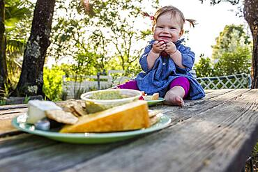 Caucasian baby girl sitting on patio table