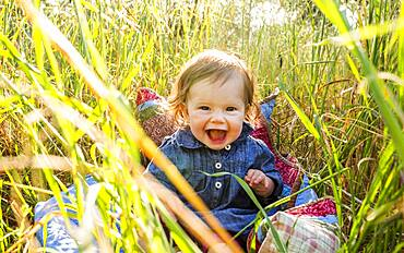 Caucasian baby girl sitting in tall grass