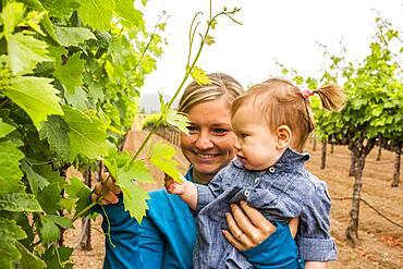 Caucasian mother and daughter admiring vine in vineyard