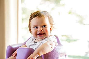 Caucasian baby girl sitting in high chair