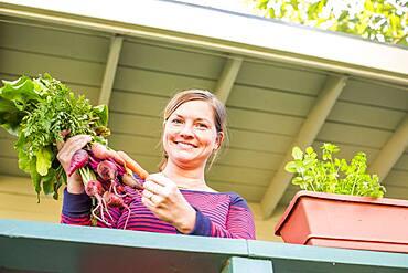 Caucasian woman holding fresh carrots on patio