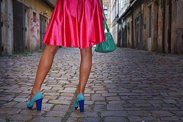 Caucasian woman wearing heels in alleyway