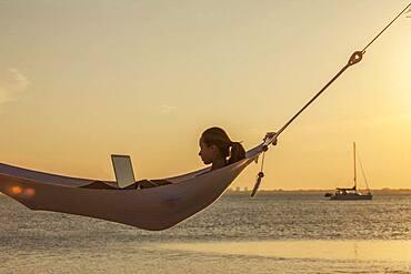 Caucasian woman using laptop in hammock