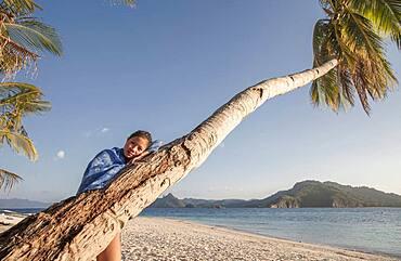 Asian woman on palm tree on beach