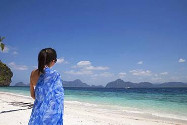 Asian woman walking on beach