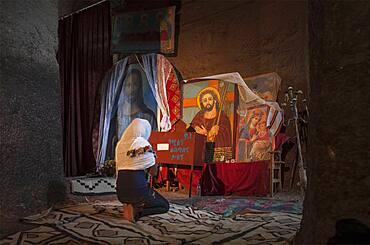 Black woman praying at shrine