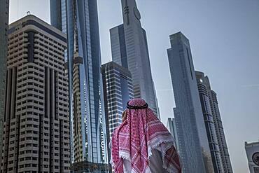 Pakistani man admiring highrise buildings in Dubai cityscape, Dubai Emirate, United Arab Emirates