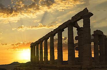 Temple of Poseidon ruins under sunset sky, Cap Sunion, Greece