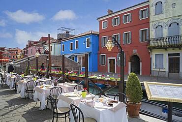 Sidewalk cafe overlooking Venice Burano canal, Veneto, Italy