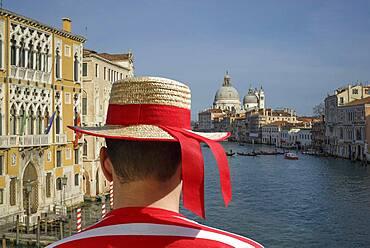 Caucasian gondolier admiring Venice cityscape, Veneto, Italy
