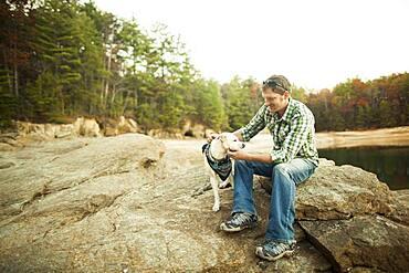 Man petting dog on rocks near lake