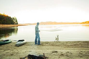 Man and dog playing in remote lake